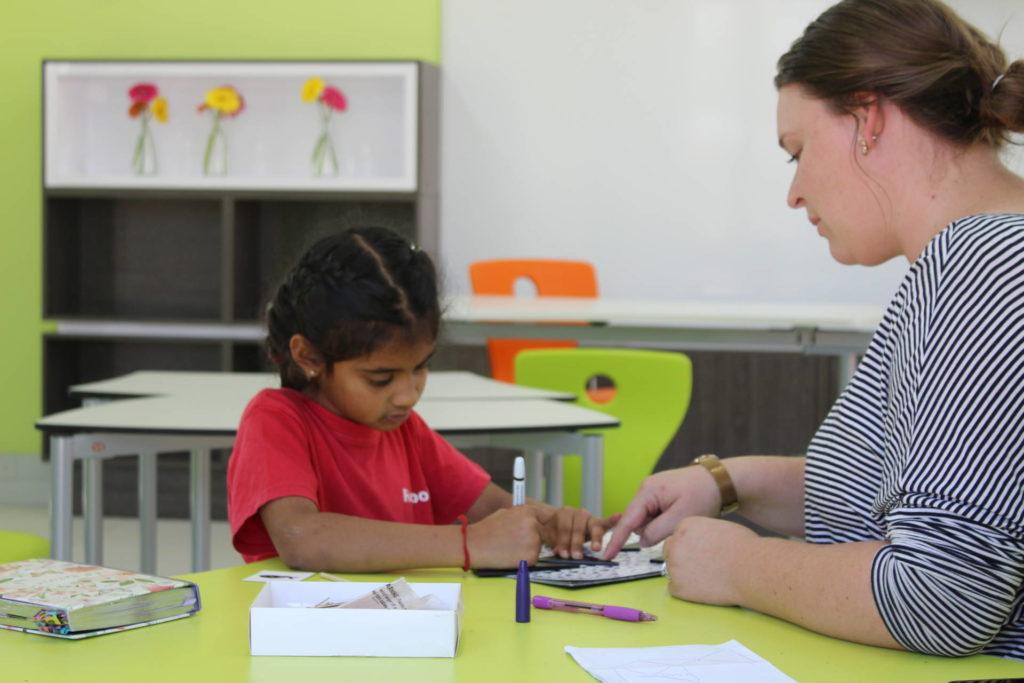 Teacher assisting student.