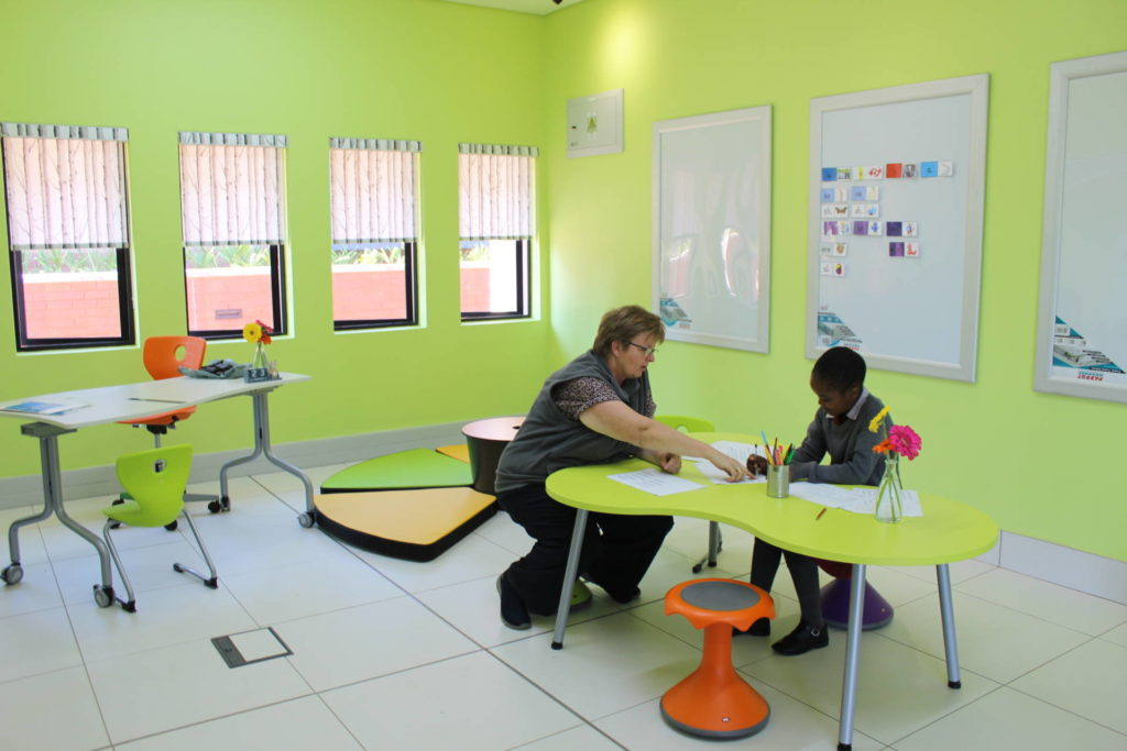 Student being assisted by teacher in a classroom.